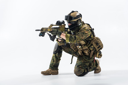 Full length side view severe defender in army clothes looking at sniper scope. Protection and armament concept Stock Photo
