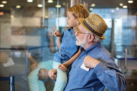 集中した祖父のサイドビュープロファイルは、彼のおじいちゃんを手にしてターミナルホールに立っています。彼はシャツのポケットにチケットを 写真素材