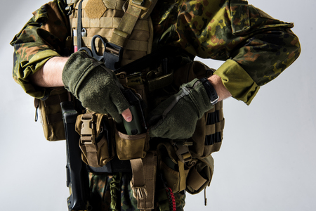 Close up soldier arms putting bombshell in special pocket in bulletproof vest. Technology and fight concept