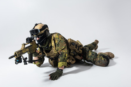 Full length portrait of calm defender watching at weapon while situating at floor. Military concept