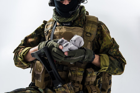 Close up soldier arms keeping teddy bear while wearing in military ammunition. Carry and conflict concept