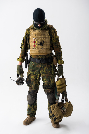 Full length portrait of serene soldier keeping ammunition in hands. Military concept
