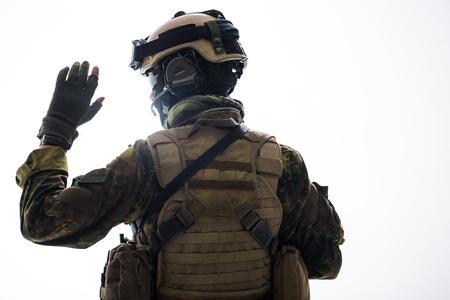 Defensor em uniforme militar, gesticulando a mão enquanto voltando para a câmera. Conceito de guerra. Isolado Foto de archivo