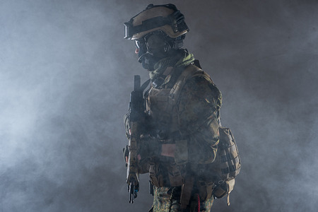 Side view orderly soldier wearing army ammunition while standing in smoke. Pacificator concept Stock Photo