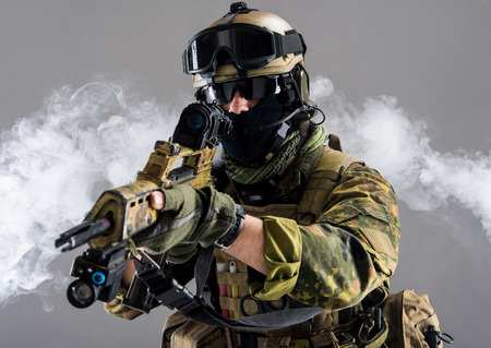 Portrait of serious soldier keeping assault rifle while standing in smoke. War concept