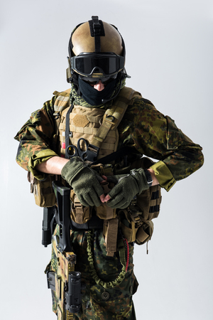 Portrait of calm peacemaker closing body armour. He wearing balaclava and helmet. Ammunition concept. Isolated