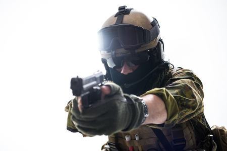 Portrait of serious peacemaker shooting with gun. Protection and military concept. Isolated and copy space Stock Photo