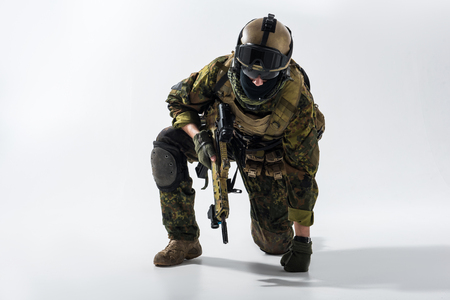 Portrait of tired soldier kneeling and leaning on arm while keeping modern weapon in hand. Military concept
