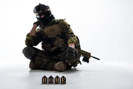 Portrait of serious defender wearing uniform while sitting on ground. He missing home. Army concept