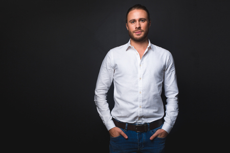 Waist up portrait of tranquil man looking at camera. Isolated on black background. Copy space in left side