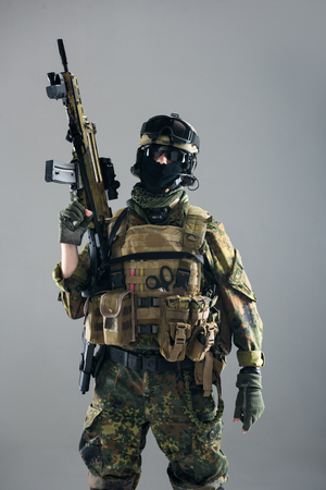 Portrait of serious man keeping assault rifle in hand. Occupation and army concept. Isolated