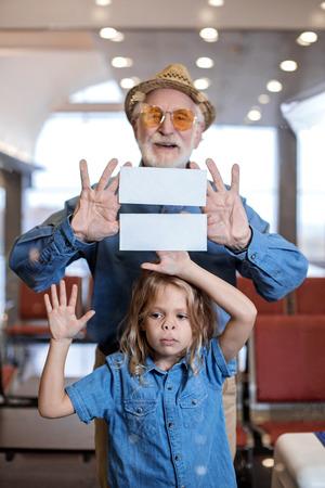 冒険に向かって喜びに満ちた白髪の祖父の肖像画は、ガラスを通してカメラを見ながら孫娘と一緒に立っています。喜びを表しながらチケットを見 写真素材