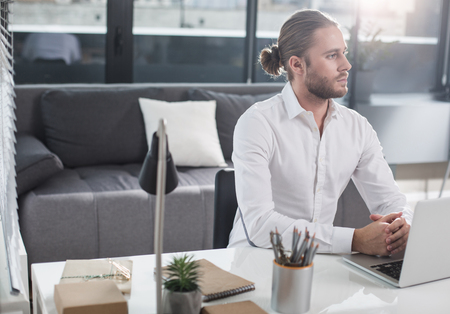 Thoughtful man sitting at the table near laptop. He is looking aside. Copy space in left side