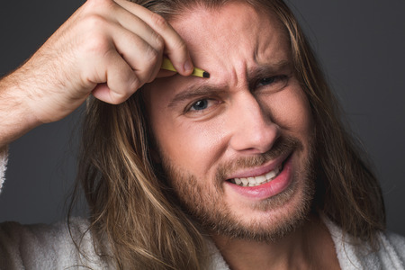 Close up portrait of stressed man using tweezers and wrinkling his face expressing pain. Isolated on grey background Stock Photo