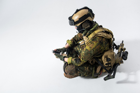 Side view calm defender typing in mobile while sitting on floor. Digital device and army concept. Copy space Stock Photo