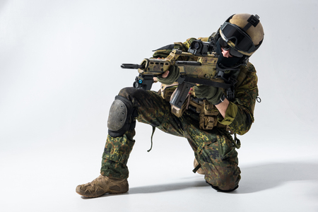Portrait of serious defender looking at sniper scope of modern weapon. Military concept Stock Photo