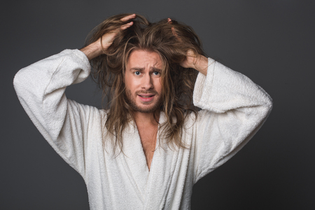 Waist up portrait of mad guy drawing his hands into tangled hair in frustration. Isolated on grey background