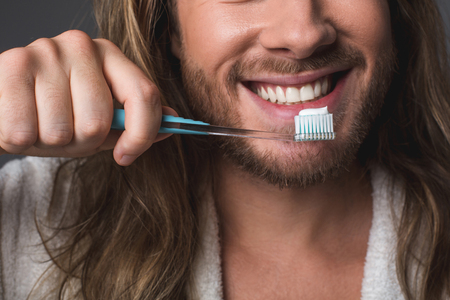 Oral hygiene. Close up of smiling guy holding toothbrush with toothpaste on top Foto de archivo - 92592661