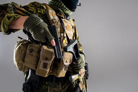 Close up male hands in military uniform holding weapon. Protection and ammunition concept. Isolated and copy space Stock Photo