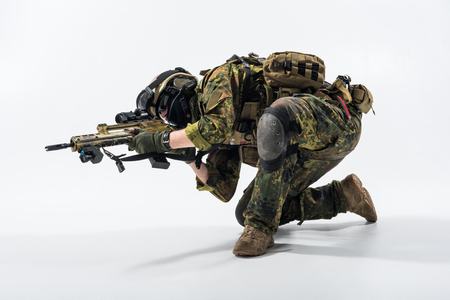 Full length severe soldier shooting firing with assault carbine. War concept