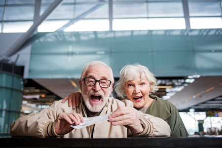 Feeling astonishment. Portrait of surprised gray-haired happy wife and husband are standing at airport while holding their tickets. They are looking at camera with wide-eyed and happy smile