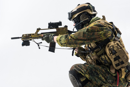 Side view severe peacemaker firing with weapon in military ammunition. Army concept