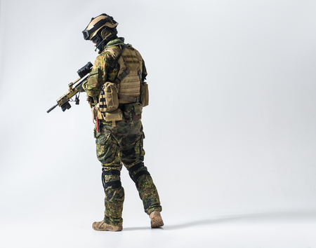 Full length side view serene defender in army clothes keeping assault rifle. Protection concept. Copy space Stock Photo