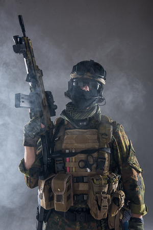 Portrait of serious soldier wearing army clothes while keeping assault rifle in arms. He locating in smoke. Military concept Stock Photo