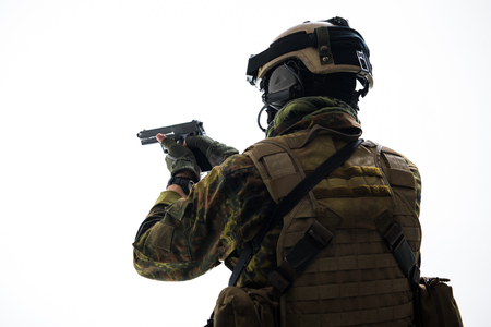 Soldier in army uniform shooting with pistol. He turning back to camera. Army concept. Isolated and copy space