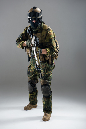 Full length portrait of serious man keeping assault rifle in hand. Army concept Stock Photo