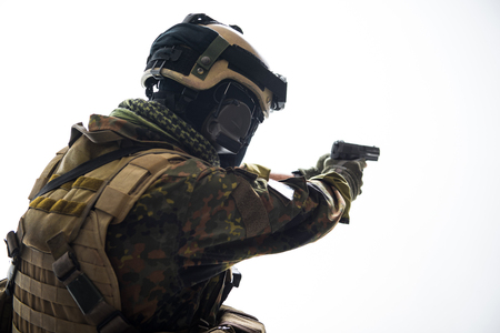 Defender shooting with gun. He wearing helmet and army uniform. Protection concept. Isolated