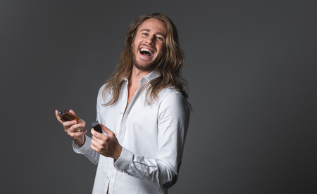Waist up portrait of cheerful longhaired man holding bottle of essence. He is looking at camera and laughing. Copy space in right side. Isolated on grey background