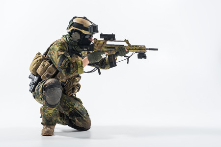 Side view stern soldier looking at sniper scope while shooting with assault carbine. War concept. Copy space