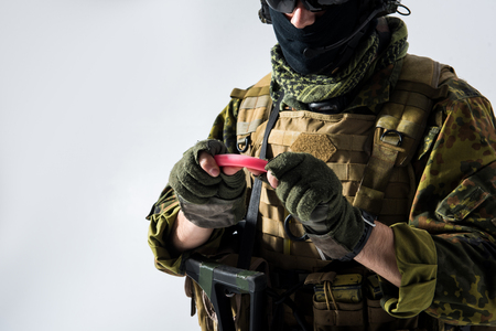 Close up defender arm holding special flashlight while wearing in ammunition. Military concept. Isolated and copy space