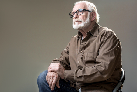 Waist up of mature man in glasses sitting on chair. His face is wistful. Isolated on grey background