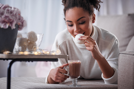 Portrait of cheerful young woman eating marshmallow and drinking cocoa. She is lying on sofa with relaxation