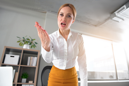 Low angle portrait of angry businesswoman flourishing arm while looking at camera. Rage and job concept