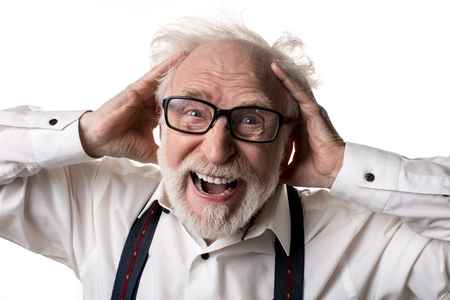 Portrait of annoyed crazy pensioner with messy hair crying and holding his hands on head. Isolated on background Stok Fotoğraf