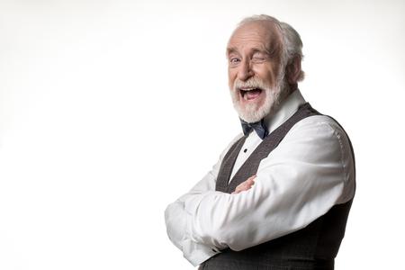 Retrato do homem idoso jesting que pisc na câmera com alegria. Copie o espaço no lado esquerdo. Isolado no fundo