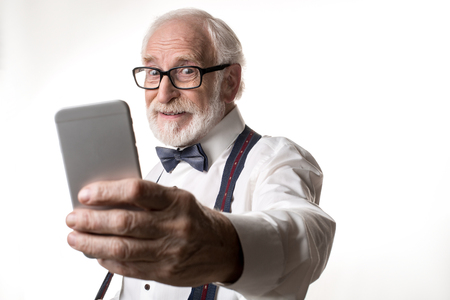 Waist up portrait of joyful elderly man making selfie, looking amused. Focus on face and phone. Isolated on background