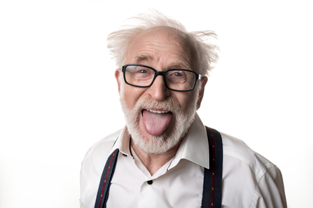 Portrait of jocular aging man with disheveled hair sticking his tongue out in Einstein manner. Isolated on background Stock fotó