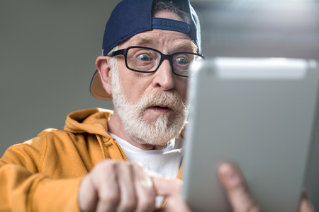 Oh my god. Surprised senior wearing cap and glasses. He is looking at pad with wonder. Isolated on grey background Stock Photo