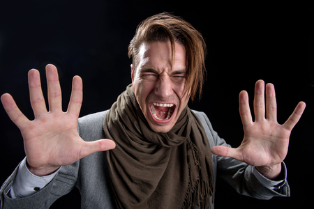 Portrait of crazy desperate man is standing and screaming loudly. He is looking at camera with anger while gesturing with hands and expressing negative emotions. Isolated background