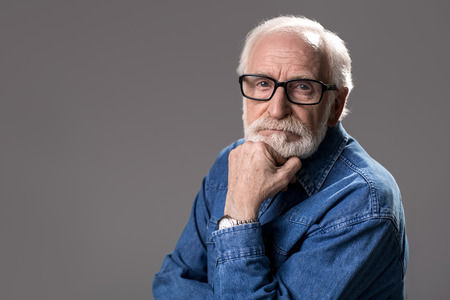 Portrait of grizzled old man looking at camera with gravity. Copy space in left side. Isolated on grey background