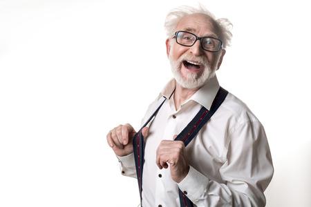 カメラを見て笑いながらサスペンダーに立つコミカルな年金受給者の肖像画をウエストアップ。左側にスペースをコピーします。バックグラウンド 写真素材
