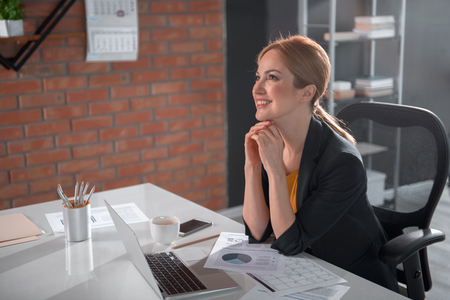 Side view pensive lady having job with notebook computer while sitting at table in office. Dreaminess concept