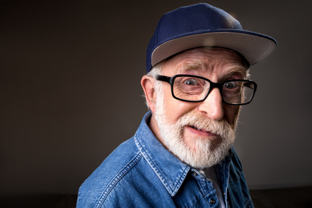 Portrait of humorous senior man gazing at camera and cringing. Standing near wall Stock Photo