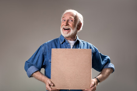 Waist up portrait of humorous elderly man holding wooden frame. Isolated on grey background