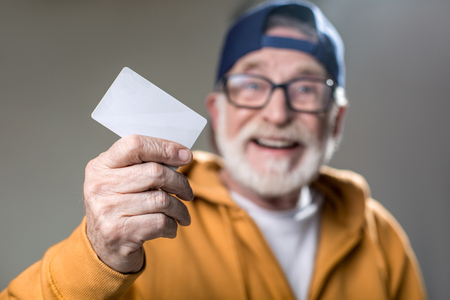 Portrait of old stylish man with smile. Focus on male hand holding bankcard. Isolated on grey background