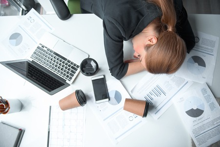 Top view serene weary female lying on desk in modern office. Mugs of beverage and different documents locating on it. Job and fatigue concept